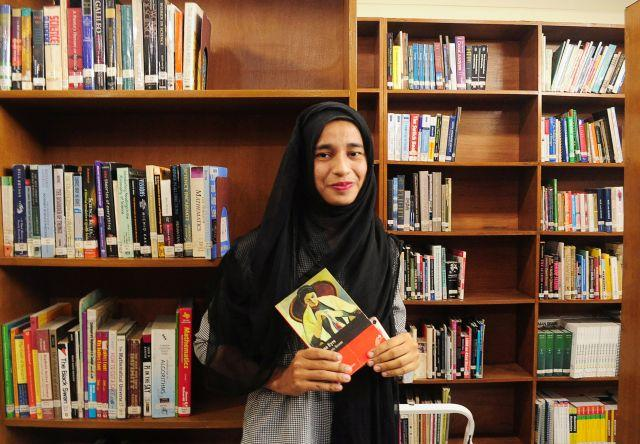 Formin Akter, a Rohingya refugee girl, holds a copy of the novel Jane Eyre, which she says is her new favourite book, inside the library of the Asian University for Women in Chittagong