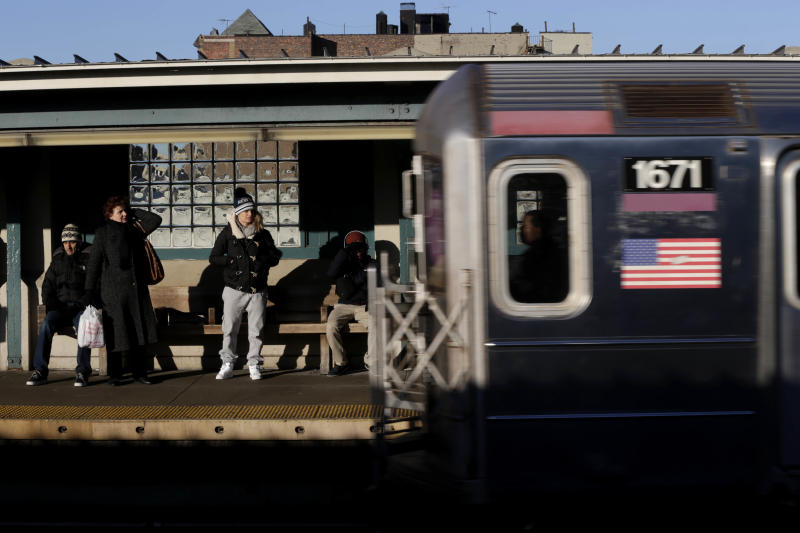 Commuters watch as a train enters the 40th St-Lowry St Station, where a man was killed after being pushed onto the subway tracks, in the Queens section of New York, Friday, Dec. 28, 2012. Police are searching for a woman suspected of pushing the man and released surveillance video Friday of her running away from the station.(AP Photo/Seth Wenig)
