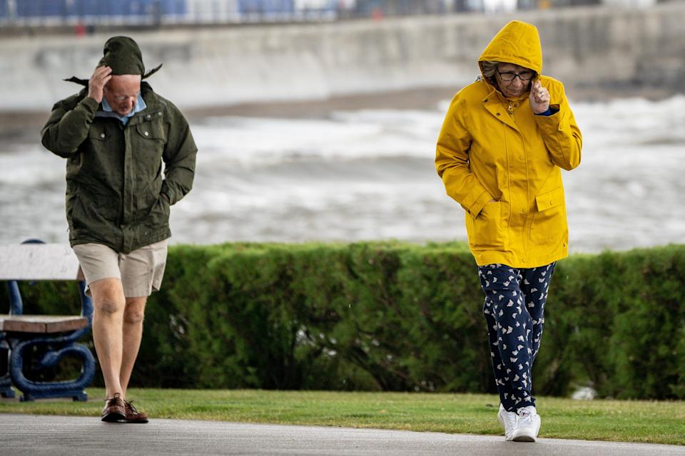 People pull down their hoods to shelter from the wind as they walk along the sea front in Porthcawl, Wales (Ben Birchall/PA). (PA Wire)