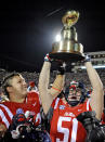 Mississippi's John Youngblood and Walker Sturgeon celebrate with the Egg Bowl trophy after an NCAA college football game against Mississippi State in Oxford, Miss., Saturday, Nov. 29, 2014. No. 18 Mississippi beat No. 4 Mississippi State 31-17. (AP Photo/Thomas Graning)