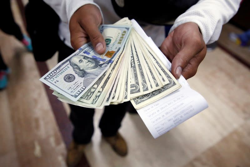FILE PHOTO: A man poses with dollars, after buying them at a money exchange in Caracas