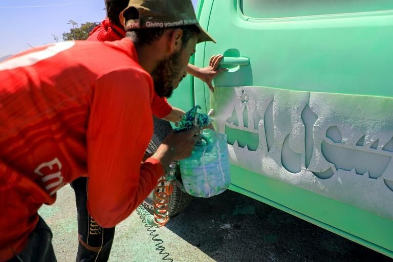 A Yemeni man sprays 'At your orders, Oh messenger of Allah' on a truck in the capital Sanaa on Saturday, as the backlash against Macron grew