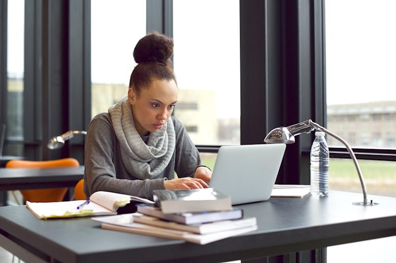 Young woman typing on laptop while staring intently at screen