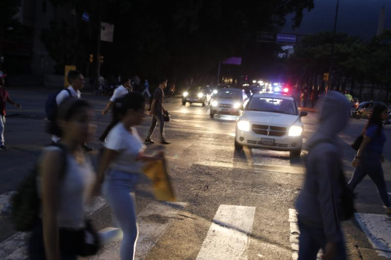 People cross a street during a blackout in Caracas, Venezuela, Monday, July 22, 2019. The lights went out across much of Venezuela Monday, reviving fears of the blackouts that plunged the country into chaos a few months ago as the government once again accused opponents of sabotaging the nation's hydroelectric power system. (AP Photo/Ariana Cubillos)