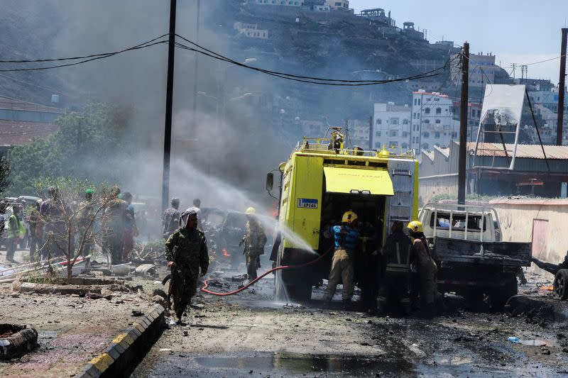 Policemen and firefighters are pictured at the scene of a blast in Aden