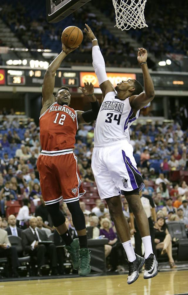 CORRECTS SPELLING OF LAST NAME TO ADRIEN FROM ADREIN - Milwaukee Bucks forward Jeff Adrien, left, has his shot blocked by Sacramento Kings forward Jason Thompson during the first quarter of an NBA basketball game in Sacramento, Calif., Sunday, March 23, 2014.(AP Photo/Rich Pedroncelli)