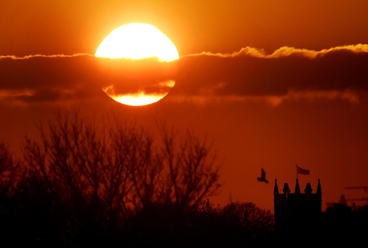 The sun balances next to St Albans Church in Earsdon, North Tyneside, as the sun set last night. PRESS ASSOCIATION Photo. Picture date: Monday April 20, 2015. Britain's is set to bask in sunshine today with temperatures expected to equal the holiday resort of Ibiza. See PA story WEATHER Hot. Photo credit should read: Owen Humphreys/PA Wire