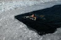 An ice swimmer braves a frozen lake on a cold winter day in Beijing