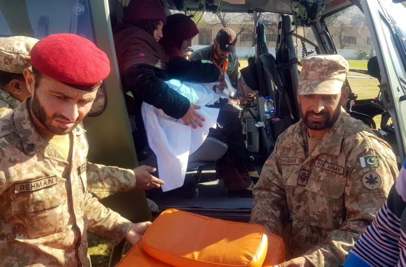 Army soldiers transport the body of six-year-old Safia Bibi in a helicopter in Muzaffarabad