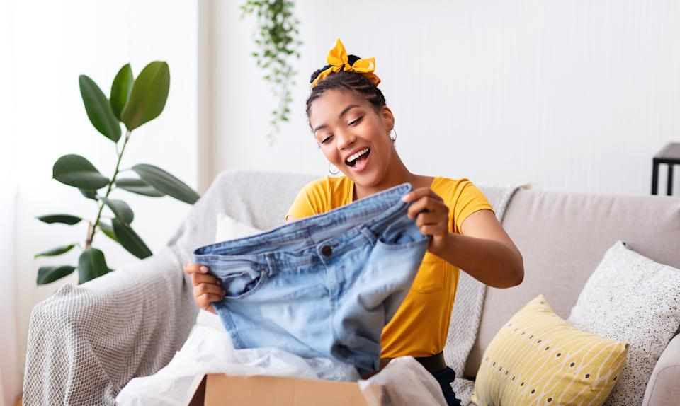 Delivery Concept. Happy black woman sitting on couch and holding jeans, unboxing cardboard package, free space