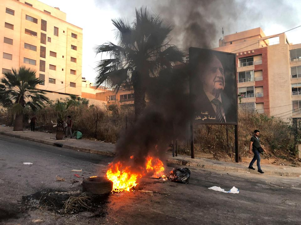 A man walks near a burning fire blocking a road during a protest against mounting economic hardships in Beirut (REUTERS)