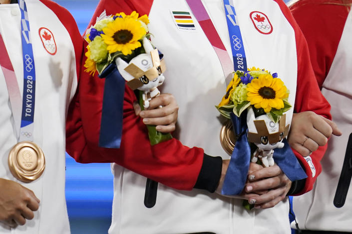 Canada team members hold flowers presented to medal winners at the medal ceremony for softball at the 2020 Summer Olympics, Wednesday, July 28, 2021, in Yokohama, Japan. (AP Photo/Sue Ogrocki)