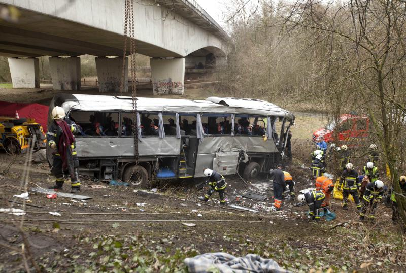 A crane lifts a bus which crashed into a ravine in Ranst, Belgium on Sunday, April 14, 2013. The Polish bus carrying Russian youngsters crashed through guardrails and off a highway onto a field below near the port city of Antwerp on Sunday, killing at least five people and leaving five more critically injured. (AP Photo/Virginia Mayo)