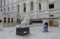 A worker cleans the Marly courtyard in the Louvre museum, in Paris, Thursday, Feb. 11, 2021. Gone are the crowds' sweltering heat, the jostling for a view and the constant snapping of cameras. It's uncertain when the world's most visited museum will reopen, after being closed on Oct. 30 in line with the French government's virus measures. (AP Photo/Thibault Camus)