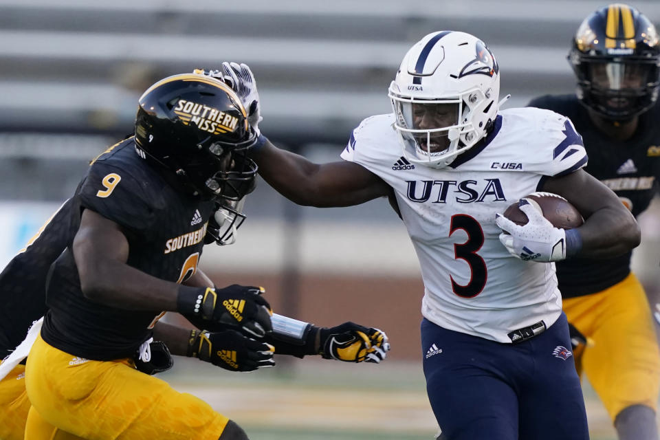 UTSA running back Sincere McCormick (3) fends off an attempted tackle by Southern Mississippi defensive back Malik Shorts (9) during the second half of an NCAA college football game, Saturday, Nov. 21, 2020, in Hattiesburg, Miss. UTSA won 23-20. (AP Photo/Rogelio V. Solis)