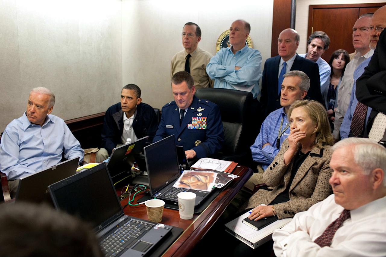 "FILE - In this May 1, 2011 image released by the White House and digitally altered by the source to obscure the details of a document on the table, President Barack Obama, second from left, Vice President Joe Biden, left, Secretary of Defense Robert Gates, right, Secretary of State Hillary Rodham Clinton, second right, and members of the national security team watch an update on the mission against Osama bin Laden in the Situation Room of the White House in Washington. A new book due out Tuesday, Oct. 16, 2012 says the president hoped to put Osama bin Laden on trial if he had surrendered during a U.S. raid. Author Mark Bowden quotes Obama as saying he thought he could make a strong political argument for giving bin Laden the full rights of a criminal defendant, to show U.S. justice applies even to him. In ""The Finish,"" Bowden writes, however, that Obama said he expected the terror leader to go down fighting. (AP Photo/The White House, Pete Souza)"