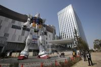 Journalists look at a full-size model of Japan's popular robot animation character Gundam standing in front of a new shopping mall in Tokyo's Odaiba waterfront area Tuesday, April 17, 2012. The 18-meter (60-foot)-tall Gundam greets shoppers at Diver City Tokyo Plaza which opens on Thursday. (AP Photo/Koji Sasahara)