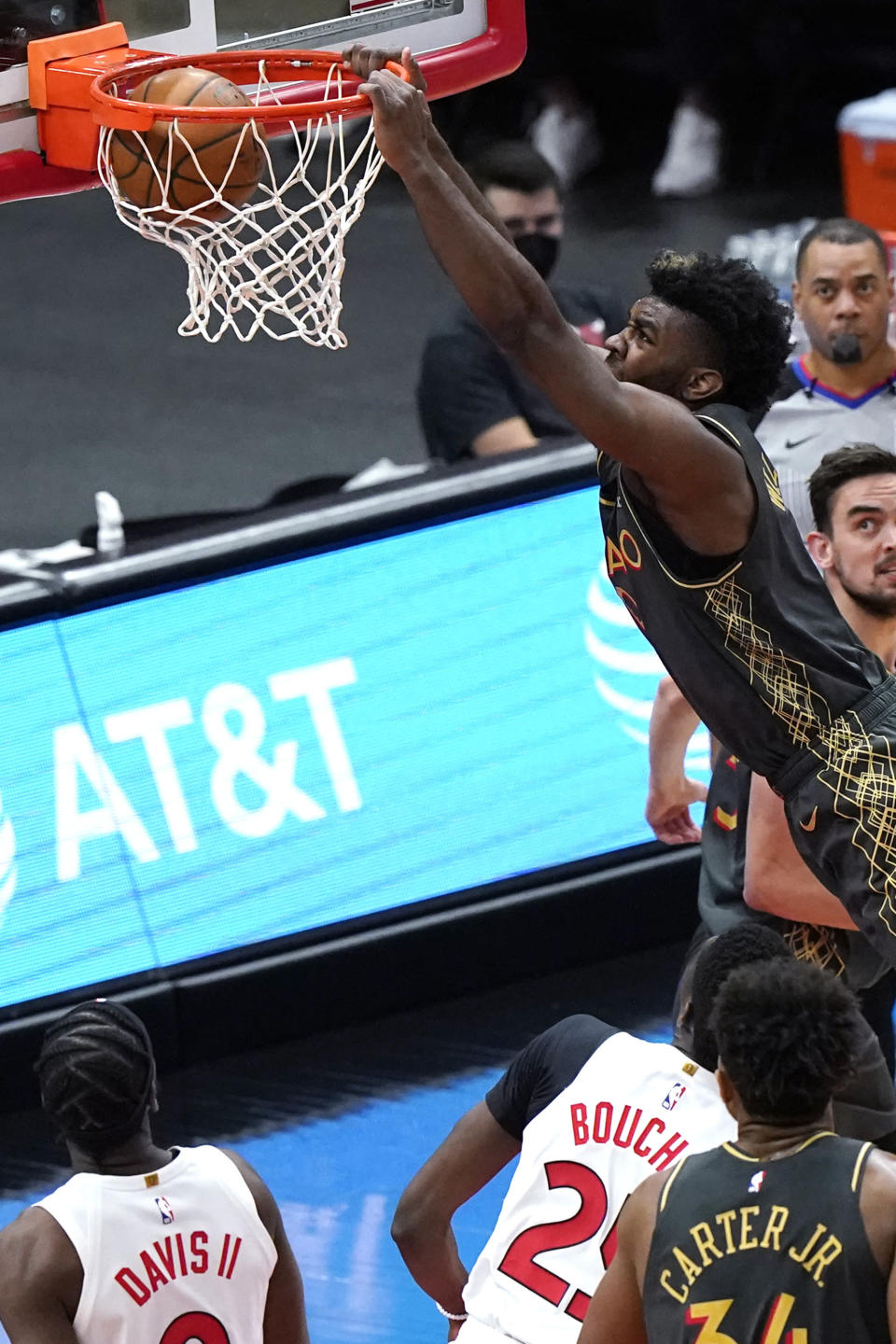 Chicago Bulls forward Patrick Williams, top, dunks as Toronto Raptors guard Terence Davis, left, and forward Chris Boucher watch during the second half of an NBA basketball game in Chicago, Sunday, March 14, 2021. (AP Photo/Nam Y. Huh)