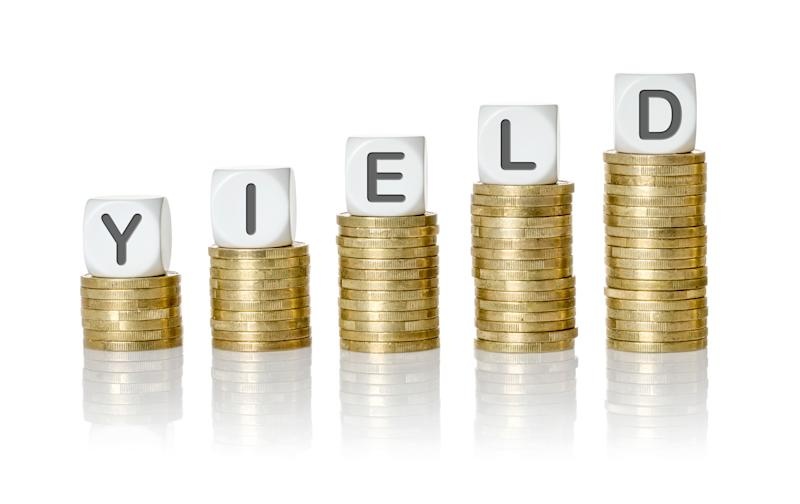 The word yield spelled out with dice sitting atop stacks of coins