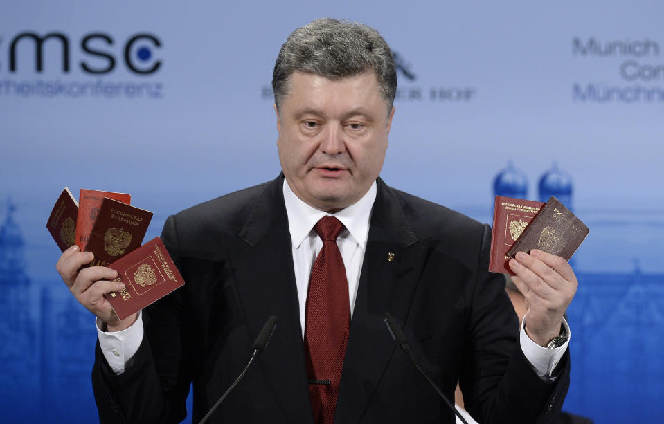 Ukraine President Petro Poroshenko shows Russian passports to demonstrate the presence of Russian troops in the Ukraine, as he addresses the 51st Munich Security Conference (MSC) in southern Germany, on February 7, 2015 (AFP Photo/Thomas Kienzle)
