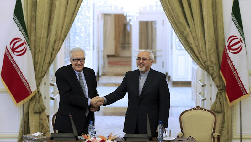 Iranian Foreign Minister Mohammad Javad Zarif, right, shakes hands with U.N. and Arab League envoy on Syria Lakhdar Brahimi as they arrive at their joint press conference in Tehran, Iran, Saturday, Oct. 26, 2013. (AP Photo)