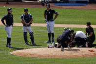 New York Yankees pitcher Masahiro Tanaka is tended to by team medical personnel after being hit by a ball off the bat of Yankees Giancarlo Stanton, left, during a baseball a workout at Yankee Stadium in New York, Saturday, July 4, 2020. (AP Photo/Adam Hunger)
