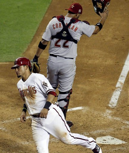 Arizona Diamondbacks' Gerardo Parra, left, scores on a bases-loaded walk as Houston Astros' Carlos Corporan flips his catcher's mask off in frustration during the fifth inning in a baseball game Friday, July 20, 2012, in Phoenix. (AP Photo/Ross D. Franklin)