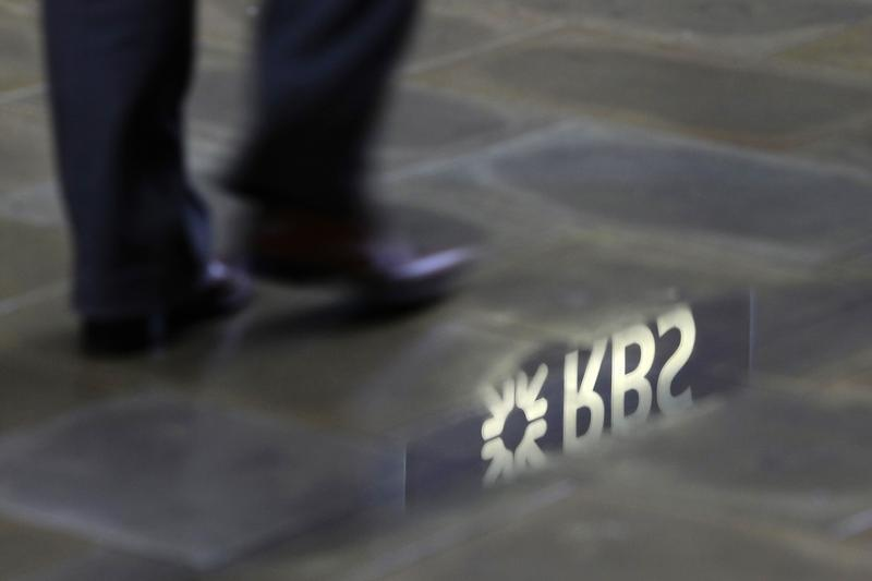 A man walks past a Royal Bank of Scotland branch reflected in a puddle in central London