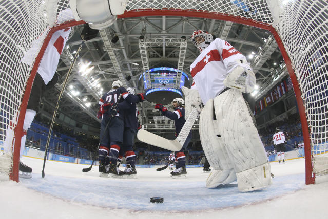 Goalkeeper Florence Schelling of Switzerland looks down at the puck as Hilary Knight of the Untied States celebrates her goal during the first period of the women's ice hockey game at the 2014 Winter Olympics, Monday, Feb. 10, 2014, in Sochi, Russia. (AP Photo/Bruce Bennett)