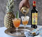 """<p>The addition of amaro brings an Italian twist to this rum punch created by Camille Wilson of <a href=""""https://www.instagram.com/thecocktailsnob_/"""" rel=""""nofollow noopener"""" target=""""_blank"""" data-ylk=""""slk:The Cocktail Snob"""" class=""""link rapid-noclick-resp"""">The Cocktail Snob</a>. It's the ultimate taste of summer.</p><p><strong>Ingredients:</strong></p><p>1 ounce pineapple juice</p><p>3/4 ounce cinnamon syrup</p><p>1/2 ounce lime juice</p><p>3/4 ounce amaro</p><p>1 1/2 ounce dark rum </p><p><strong>Directions:</strong></p><p> Combine all ingredients in a cocktail shaker with ice. Shake until chilled. Pour into a glass. Garnish with pineapple frond.</p>"""