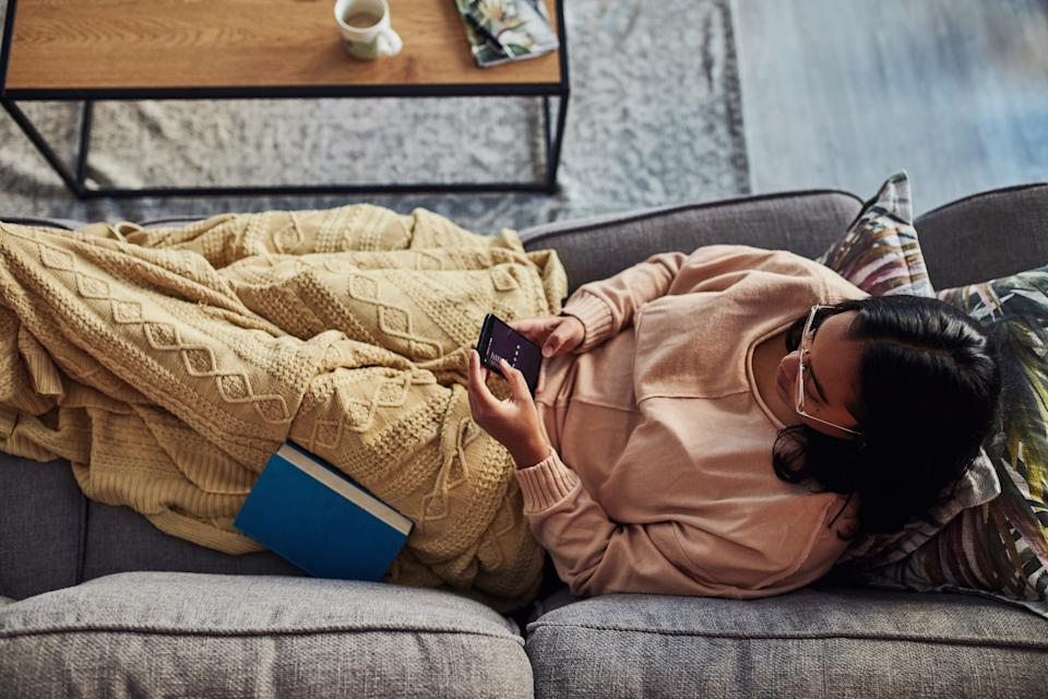 High angle shot of a young woman using a smartphone on the sofa at home