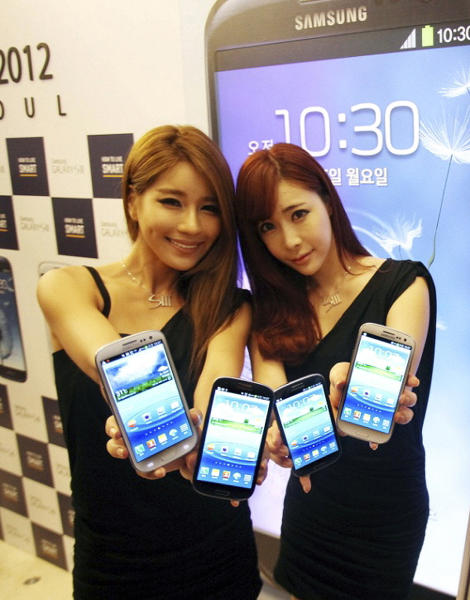 In this photo released by Samsung Electronics Co., models display Samsung Electronics' newest smartphone Galaxy S III during its world tour in Seoul, South Korea, Monday, June 25, 2012. Samsung Electronics, the world's top mobile phone maker, said Monday it expects global sales of the latest Galaxy smartphone to surpass 10 million in July even as it struggles to keep up with demand because of component shortages. (AP Photo/Samsung Electronics) NO SALES