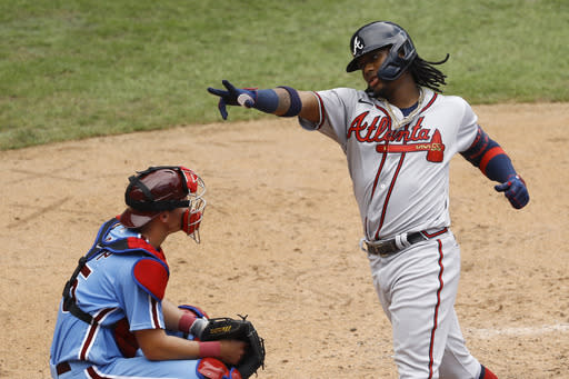 Atlanta Braves' Ronald Acuna Jr., right, reacts past Philadelphia Phillies catcher Andrew Knapp after hitting a two-run home run off relief pitcher Deolis Guerra during the fifth inning of the first baseball game in a doubleheader, Sunday, Aug. 9, 2020, in Philadelphia. (AP Photo/Matt Slocum)