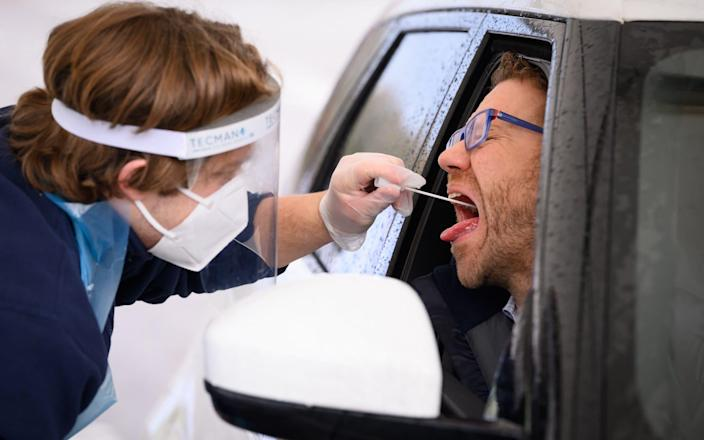 Nick Markham, the founder of ExpressTest, reacts as he takes a PCR swab test at Gatwick Airport on November 27, 2020 - Leon Neal / Getty