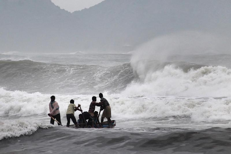 Indian fishermen negotiate their skiff through rough waves ahead of Cyclone Hudhud in Visakhapatnam on October 11, 2014 (AFP Photo/)