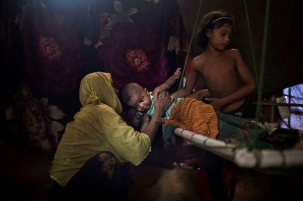 PHOTO: M's daughter, right, hands over her brother to their mother in their shelter in Kutupalong refugee camp in Bangladesh. 'M' was raped by six soldiers from Myanmar's security forces after they strangled her 2-year-old son to death, June 26, 2018. (Wong Maye-E/AP)