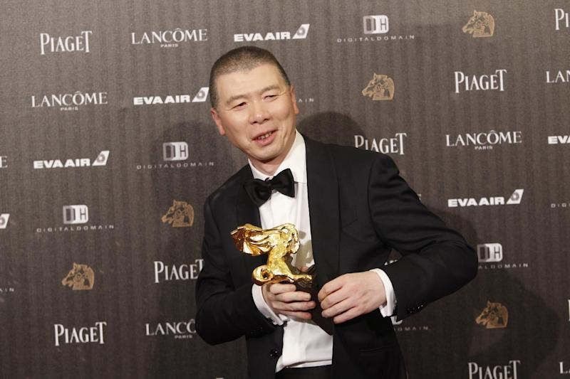 """Chinese director Feng Xiaogang holds his award for Best Director at the 53rd Golden Horse Awards in Taipei, Taiwan, Saturday, Nov. 26, 2016. Feng won for the film """"I Am Not Madame Bovary"""" at this year's Golden Horse Awards -the Chinese-language film industry's biggest annual events. (AP Photo/Chiang Ying-ying)"""