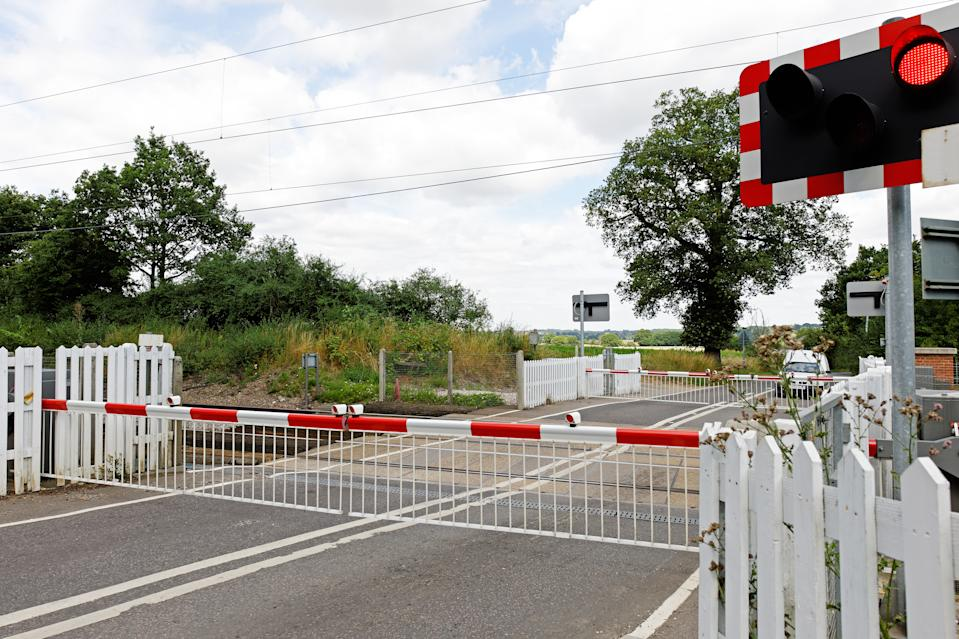 A railway level crossing in the UK countryside, with barriers closed and lights flashing