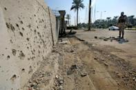 A member of the Iraqi security forces inspects damage from a volley of rockets that slammed into Baghdad after a month-long truce on attacks against the US embassy