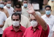 Sri Lanka's President Rajapaksa wears a protective mask as he waves to supporters while leaving a polling station in Colombo