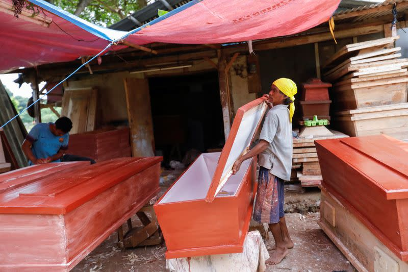 Suherman, a 45-year-old coffin maker, prepares a coffin ordered to be donated for the coronavirus disease (COVID-19) victims at a workshop inside a funeral complex in Jakarta