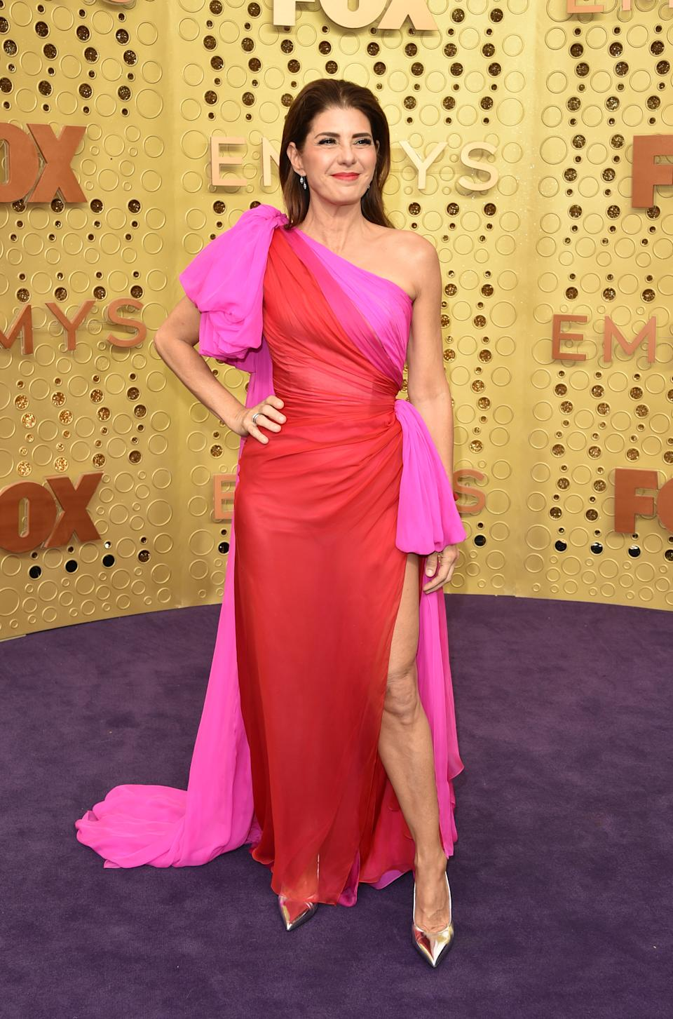 The Oscar-winning actress rocked the biggest fashion trend of the night, arriving in a pink and red asymmetrical gown with thigh-high slit. [Photo: Getty]
