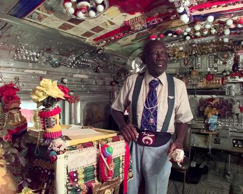 "In this 1998 photo,  Rev. H.D. Dennis, poses inside ""The House of Prayer,"" an ornately decorated school bus at his home at Margaret's Grocery near Vicksburg, Miss. The Rev. Herman ""Preacher"" Dennis, who turned a Mississippi Delta grocery store into a folk-art castle that became a roadside attraction, has died, Tuesday, Sept. 4, 2012. He was 96. (AP Photo/The Clarion-Ledger)  NO SALES"