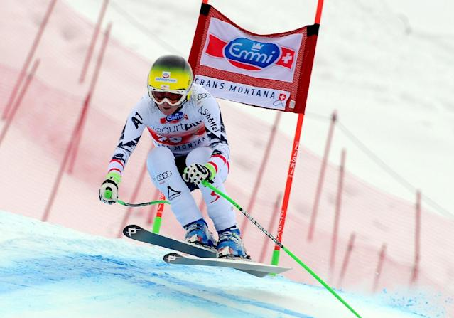 Austria's Andrea Fischbacher clears a gate on her way to win an alpine ski, World Cup women's downhill, in Crans Montana, Switzerland, Sunday, March 2, 2014. (AP Photo/Pier Marco Tacca)