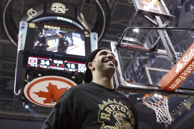 Rapper Drake stands on the court at the end of the first quarter as Toronto Raptors take on Brooklyn Nets in NBA basketball action in Toronto on Saturday Jan. 11 , 2014 (AP Photo/The Canadian Press, Chris Young)