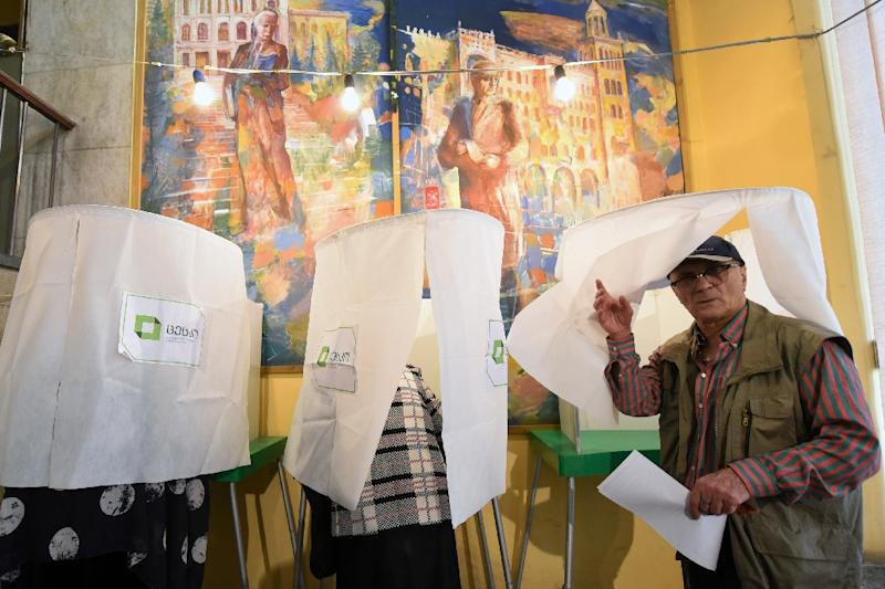A man leaves a voting booth at a polling station in Tbilisi on October 8, 2016 (AFP Photo/Vano Shlamov)