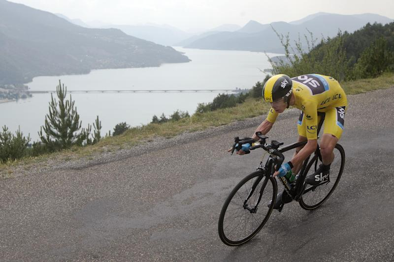 Stage winner Christopher Froome of Britain, wearing the overall leader's yellow jersey, passes lake Serre-Poncon during the seventeenth stage of the Tour de France cycling race an individual time trial over 32 kilometers (20 miles) with start in Embrun and finish in Chorges, France, Wednesday July 17, 2013. (AP Photo/Laurent Cipriani)