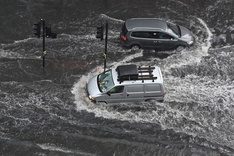 TOPSHOT - Vehicles drive through deep water on a flooded road in The Nine Elms district of London on July 25, 2021 during heavy rain. - Buses and cars were left stranded when roads across London flooded on Sunday, as repeated thunderstorms battered the British capital. (Photo by JUSTIN TALLIS / AFP) (Photo by JUSTIN TALLIS/AFP via Getty Images)