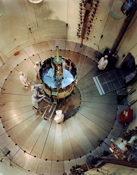"NASA's International Sun-Earth Explorer (ISEE-3) was undergoing testing and evaluation inside Goddard's dynamic test chamber when this photo was taken. Working inside a dynamic test chamber, Goddard engineers wear protective ""clean room"" clothi"