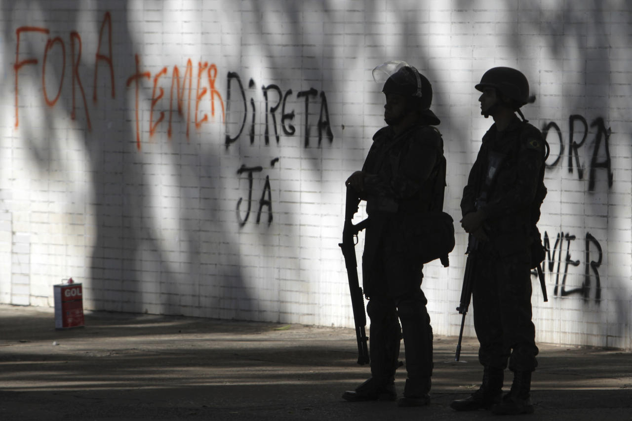 """Soldiers stand guard outside a federal building where graffiti says in Portuguese """"Get out Temer"""" and """"Direct elections now"""" in Brasilia, Brazil, Thursday, May 25, 2017. Brazil's President Michele Temer on Thursday cancelled an order to deploy the military to the streets of the capital after criticism that the move was excessive and merely an effort to hold onto power amid increasing calls for his resignation. (AP Photo/Eraldo Peres)"""